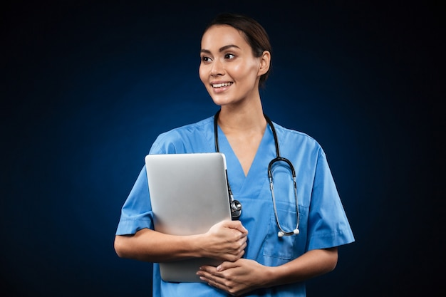 Mooie dame arts die met laptop computer opzij kijkt
