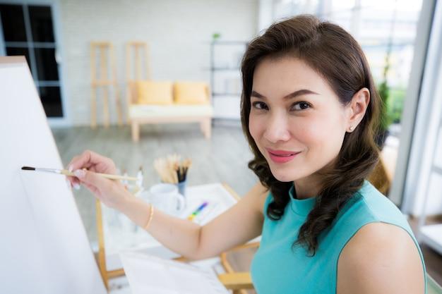 Mooie dame aziatische vrouw zitten en gebruik een borstel om foto in de kamer pijn te doen. idee voor hobby, ontspanning of kunstenaarswerk vanuit huis.