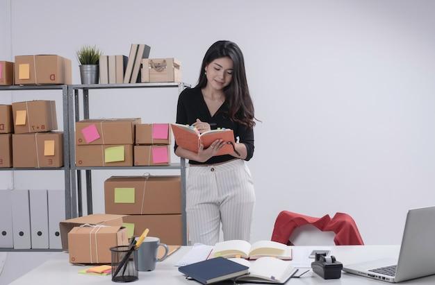 Mooie dame bestelling controleren en schrijven op boek, voorbereiden op verpakking, werkende e-commerce, zakenvrouw