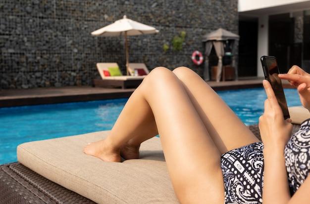 Mooie dame die celtelefoon met behulp van die op stoel door zwembad op vakantie liggen.