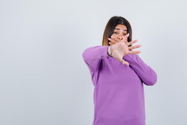 Mooie dame die de mond bedekt met de hand, geen gebaar toont in de trui en er geschokt uitziet, vooraanzicht.