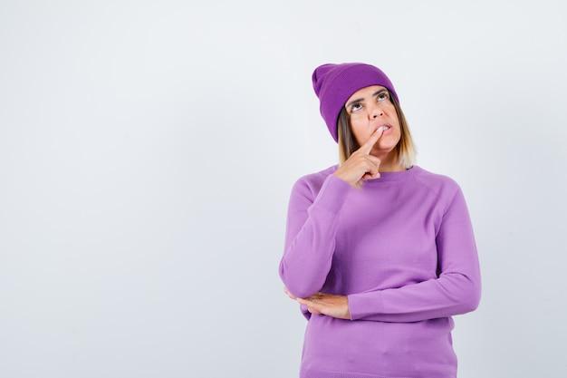Mooie dame die de vinger op de tanden houdt in de trui, muts en er gepreoccupeerd uitziet, vooraanzicht.