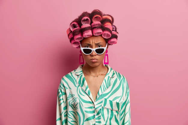 Mooie dame die geïsoleerde haarkrulspelden draagt