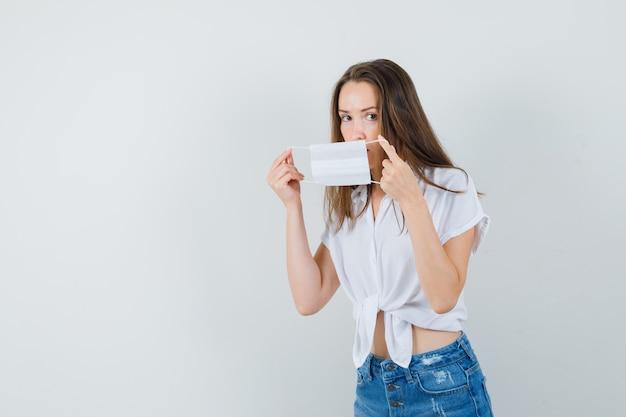 Mooie dame die gezichtsmasker in witte blouse, jeans, vooraanzicht draagt. vrije ruimte voor uw tekst