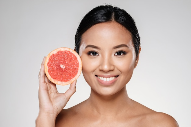 Mooie dame die grapefruitplak toont