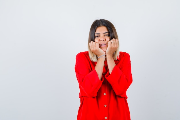 Mooie dame die haar gezicht op haar handen in een rode blouse dempt en er nieuwsgierig uitziet. vooraanzicht.