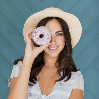 Mooie dame die haar oog bedekt met een donut