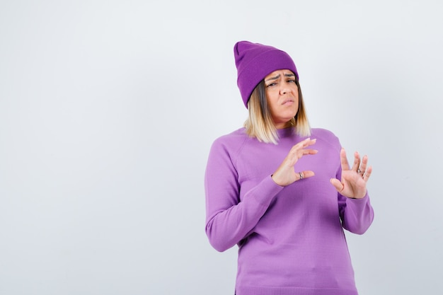 Mooie dame die handen opsteekt om zichzelf te verdedigen in trui, muts en onbeschermd, vooraanzicht.