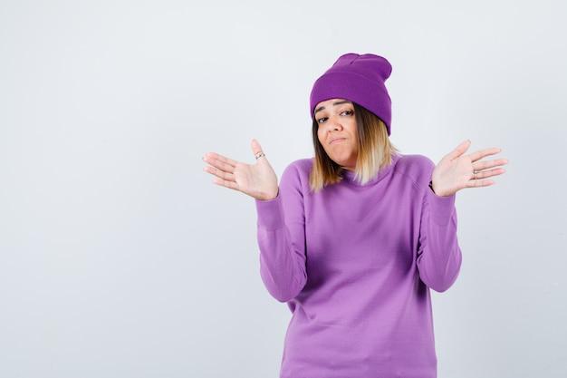 Mooie dame die hulpeloos gebaar in trui toont en hulpeloos kijkt. vooraanzicht.
