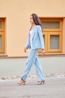 Mooie dame die in hemelsblauw broekpak op straat loopt