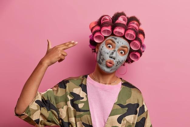 Mooie dame die masker voor gezichtszorg draagt die geïsoleerde haarkrulspelden draagt