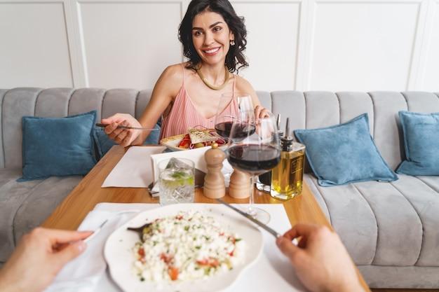 Mooie dame die naar meneer kijkt en glimlacht terwijl ze aan tafel zit met heerlijk eten en wijn
