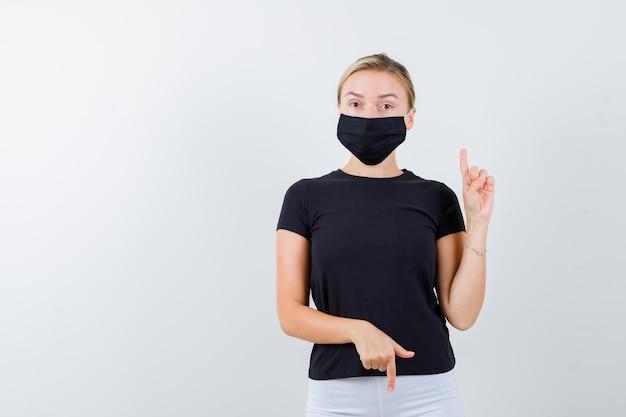 Mooie dame die op en neer wijst in zwart t-shirt, zwart masker geïsoleerd