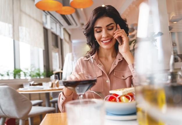 Mooie dame die op mobiele telefoon praat en glimlacht terwijl ze aan tafel zit met eten en wijn
