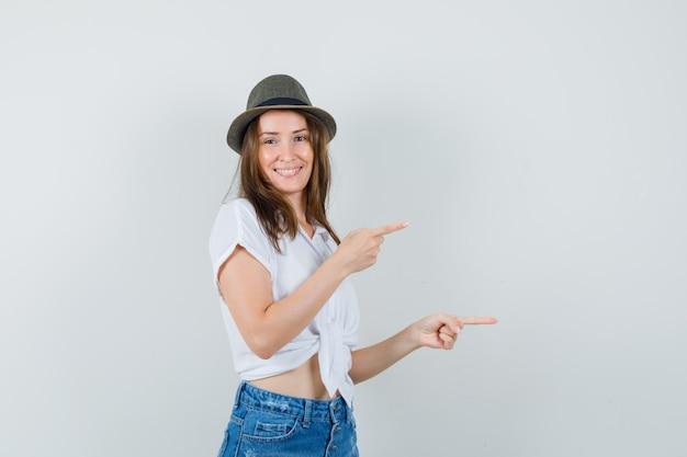 Mooie dame die opzij wijst in witte blouse, hoed en vrolijk, vooraanzicht kijkt.