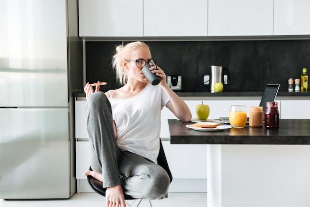 Mooie dame die thee drinkt en brood met jam in de ochtend eet