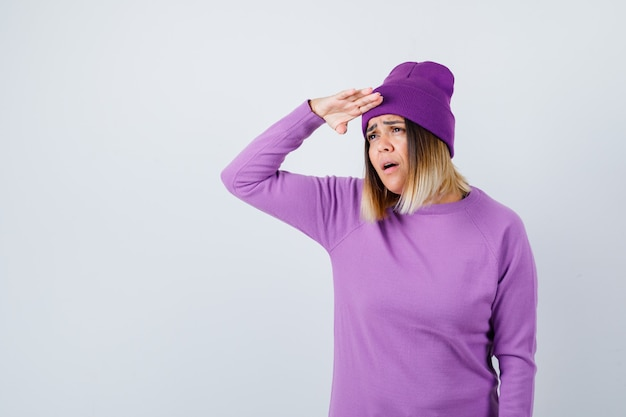 Mooie dame die ver weg kijkt met de hand over het hoofd in trui, muts en verbaasd kijkt. vooraanzicht.