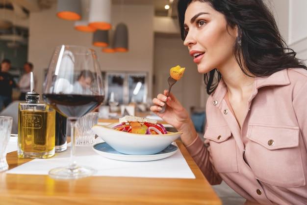 Mooie dame die verse salade eet en wegkijkt terwijl ze aan tafel zit met eten en wijn