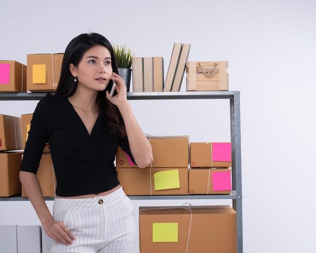 Mooie dame die vooraan brievenbusplank staat, zaken met mobiele telefoon spreekt. werkende e-commerce