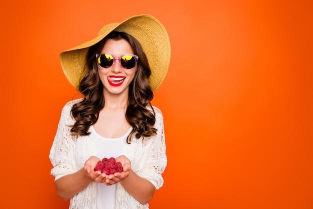 Mooie dame geniet van de zomervakantie met verse frambozen hongerige liklippen dragen pamela hoed