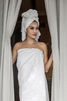 Mooie dame gewikkeld in handdoeken na het douchen