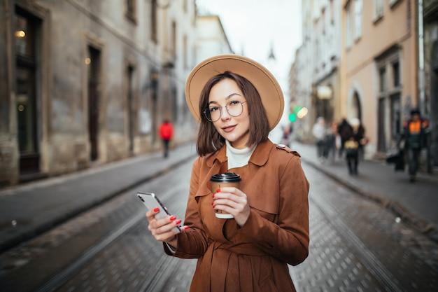 Mooie dame heeft een videocall en drinkt koffie terwijl ze buiten in de stad loopt