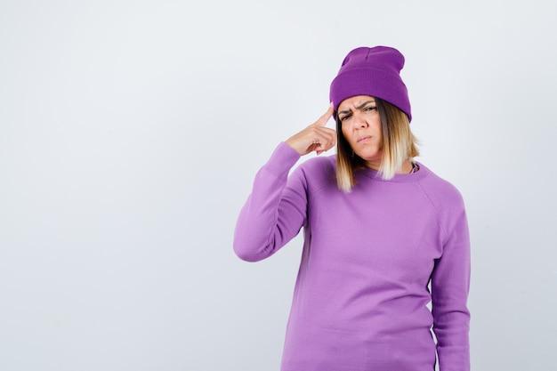 Mooie dame houdt de vinger op het hoofd in de trui, muts en kijkt verbaasd, vooraanzicht.