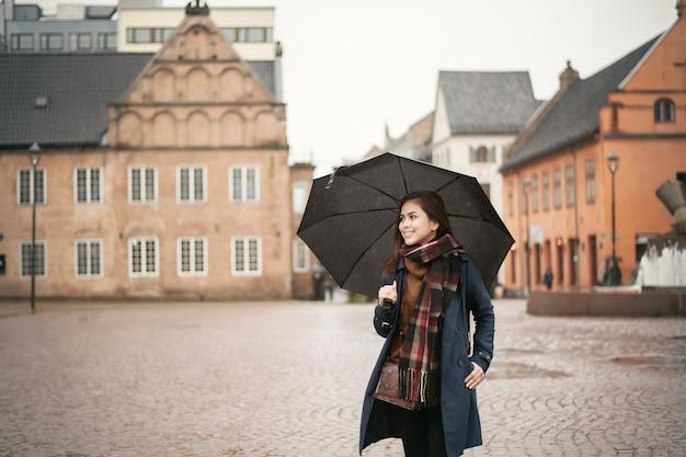 Mooie dame houdt een paraplu in de regenachtige dag