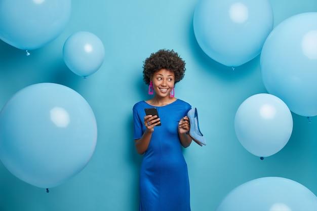Mooie dame in blauwe jurk, houdt schoenen met hoge hakken vast, houdt mobiele telefoon vast, verjaardagsfeestje, omringd door heliumballonnen, kiest outfit voor speciale gelegenheid, geniet van evenement
