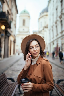 Mooie dame in bruine jas praten op mobiele telefoon buiten lopen in koude herfstdag