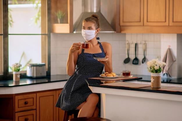 Mooie dame in een medisch masker zit in de keuken en drinkt kruidenthee. quarantaine. blijf thuis. zelfisolatie