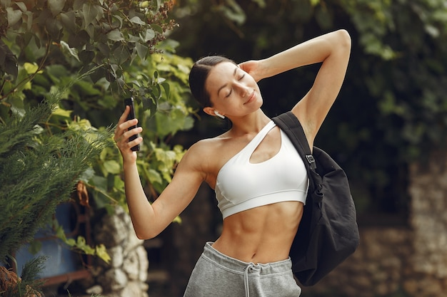 Mooie dame in een park. brunette bereidt zich voor op yoga. meisje in een sportpak.