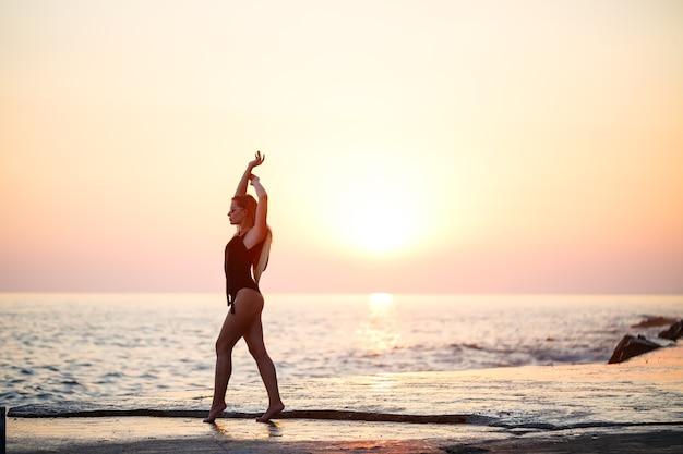 Mooie dame in een zwart zwempak aan de kust, lachend gezicht, met een strohoed op haar schouders. gouden zonsonderganglicht