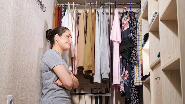 Mooie dame in grijs t-shirt probeert tevergeefs stijlvolle kleding te vinden en raakt gefrustreerd in ruime inloopkast thuis close-up