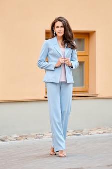 Mooie dame in hemelsblauw broekpak op straat