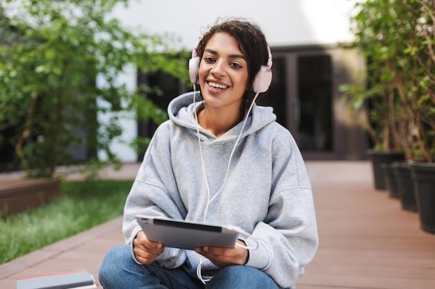 Mooie dame in hoofdtelefoons met tablet in handen zitten en gelukkig
