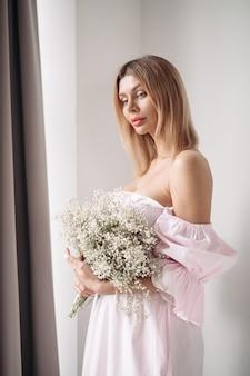 Mooie dame in jurk met bloemenboeket terwijl ze ernaar kijkt in de woonkamer thuis. romantisch begrip. lifestyle-concept