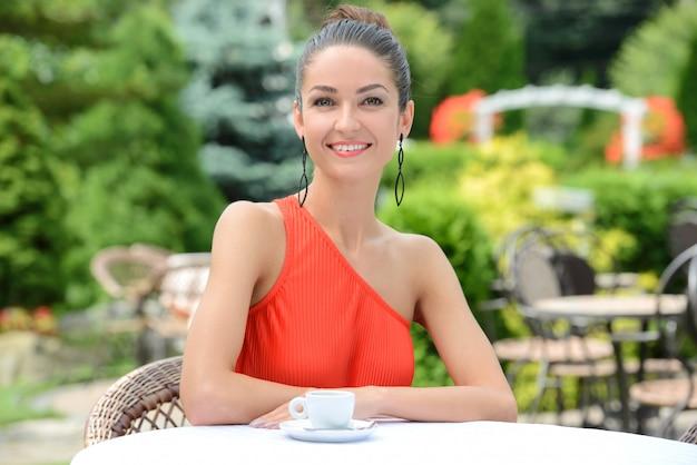 Mooie dame in kleurrijke jurk, koffie drinken.