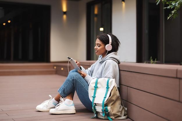 Mooie dame in koptelefoon zittend op de vloer met tablet in handen en grote rugzak in de buurt van tijd doorbrengen op de binnenplaats van de universiteit