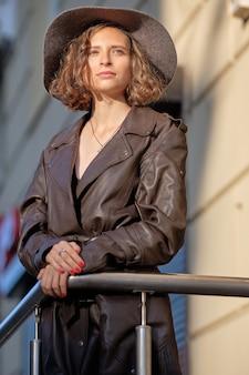Mooie dame in lange vintage jas mier hoed staande op balkon