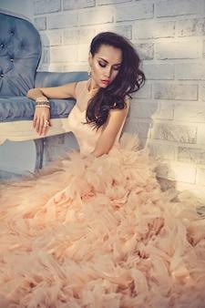 Mooie dame in prachtige couture jurk op sofa
