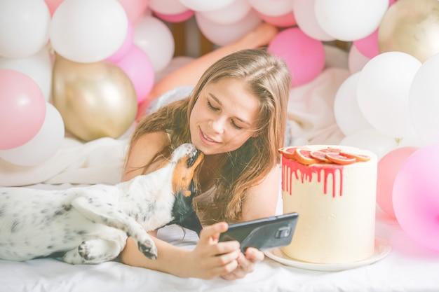 Mooie dame in pyjama selfie maken in haar slaapkamer met behulp van telefoon en haar hond kussen.