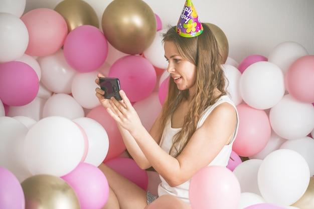 Mooie dame in pyjama selfie maken in haar slaapkamer met behulp van telefoon. fijne verjaardag.