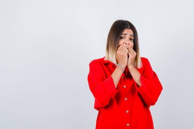 Mooie dame in rode blouse die handen op de mond houdt en er bang uitziet, vooraanzicht.