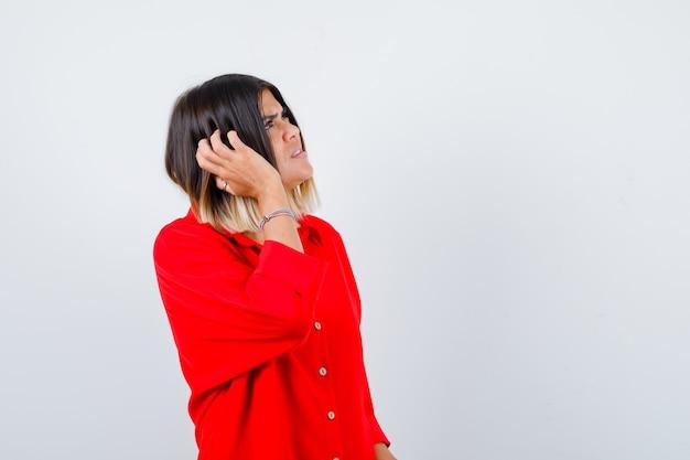 Mooie dame in rode blouse die hoofd krabt, omhoog kijkt en vergeetachtig kijkt, vooraanzicht.