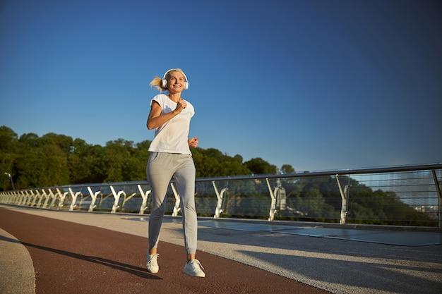 Mooie dame in sportkleding die naar muziek luistert via een draadloze koptelefoon en glimlacht tijdens het joggen op de brug