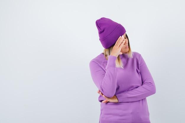 Mooie dame in trui, muts die de hand op het hoofd houdt en er depressief uitziet, vooraanzicht.
