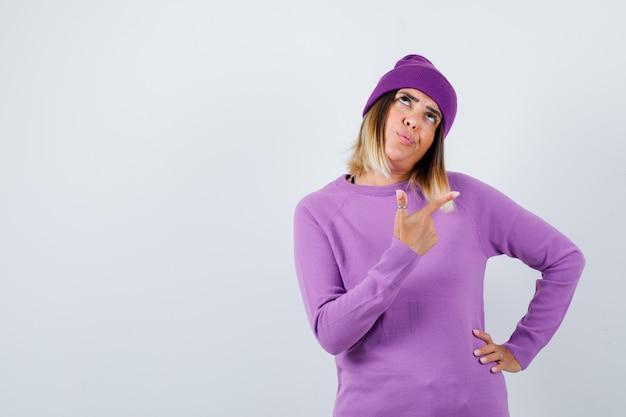Mooie dame in trui, muts die naar de rechterbovenhoek wijst en er zelfverzekerd uitziet, vooraanzicht.