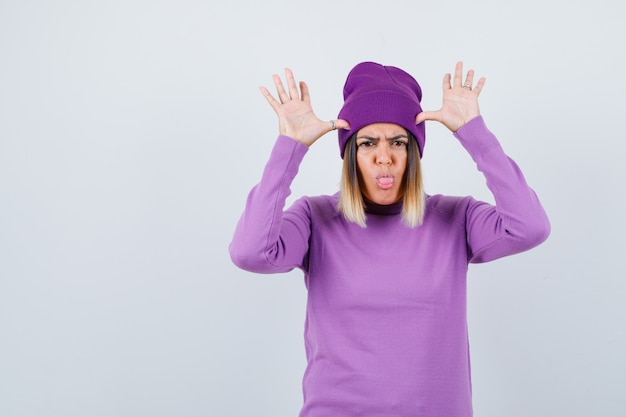 Mooie dame in trui, muts met handen in de buurt van het hoofd als oren, tong uitsteekt en er chagrijnig uitziet, vooraanzicht.