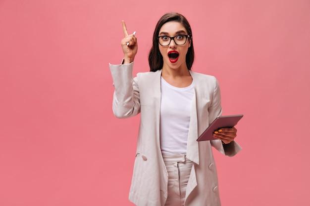 Mooie dame in wit stijlvol pak en bril heeft cool idee en vormt met computertablet op geïsoleerde roze achtergrond.